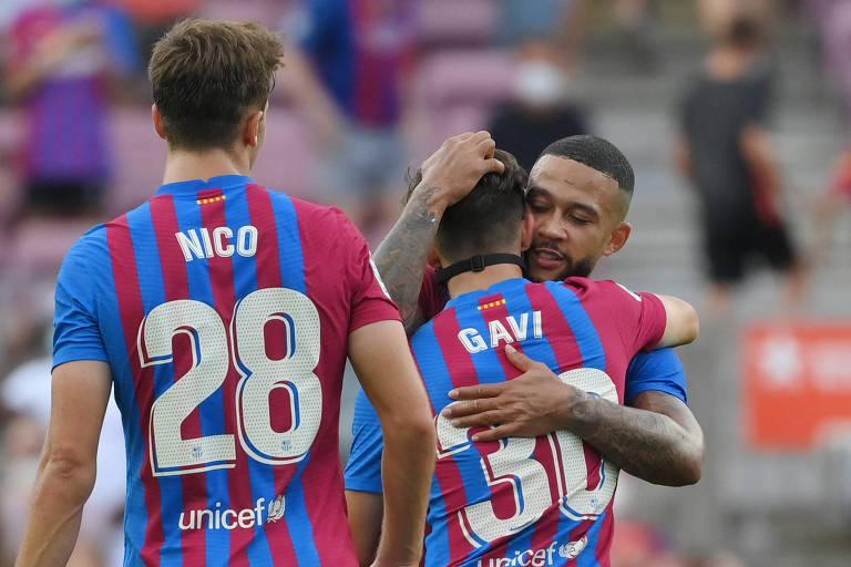 Gavi é abraçado por Memphis Depay após gol do Barcelona sobre o Getafe, pelo Campeonato Espanhol