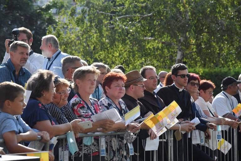 Pessoas seguram bandeiras da Eslováquia e do Vaticano antes da chegada do Papa Francisco ao centro de Belém para desabrigados em Bratislava - 65% da população eslovaca é católica