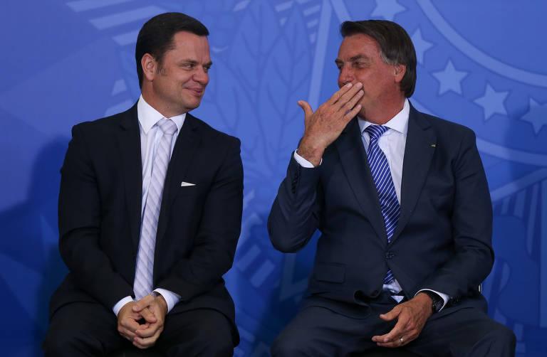 O presidente Jair Bolsonaro conversa com o ministro Anderson Torres (Justiça) em cerimônia do programa Habite Seguro, no Palácio do Planalto, em Brasília