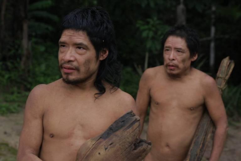 Dois indígenas diante de árvores verdes