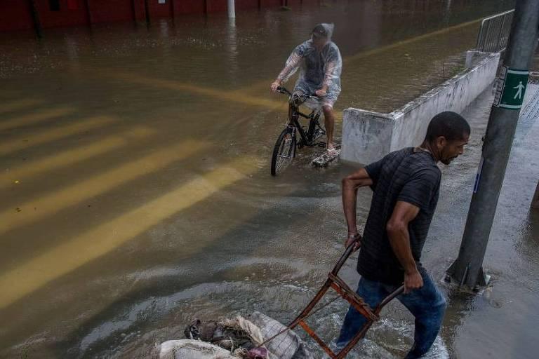 Em destaque, um homem empurra um carrinho em uma rua alagada. Ao fundo, outro homem usando capa de chuva anda em uma bicicleta