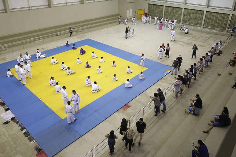 Vista geral do interior do ginásio Sarah Menezes, em Teresina, com pessoas sentadas no tatame antes de aula de judô