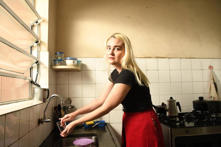 Giulianna é uma mulher branca e loira; e está olhando para foto enquanto sai apenas um filete de água de uma torneira na cozinha