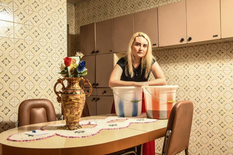 Mulher loira atrás de uma mesa apoiada em dois baldes, que usa para reservar água