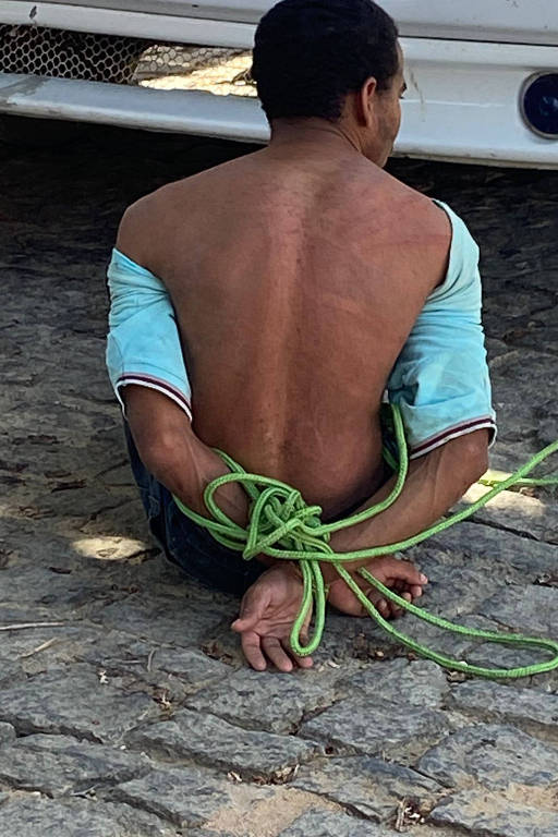 Imagem mostra homem com as mãos para trás, amarradas com uma corda na cor verde