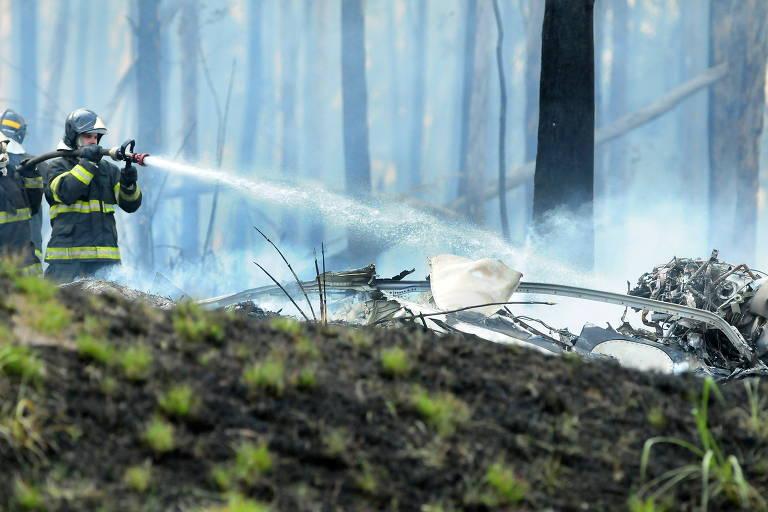 bombeiro joga jato d'água em escombros, de onde sai fumaça