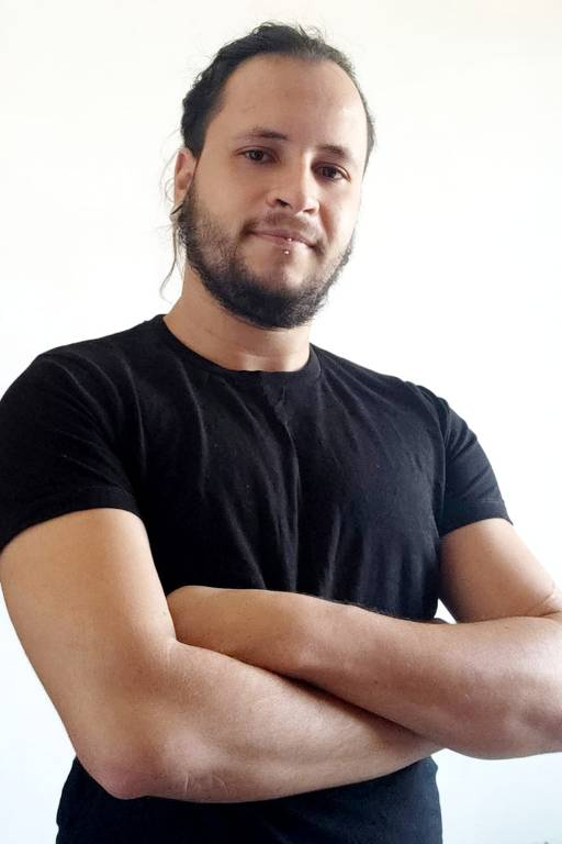Homem vestindo camiseta preta olha para a câmera de braços cruzados.