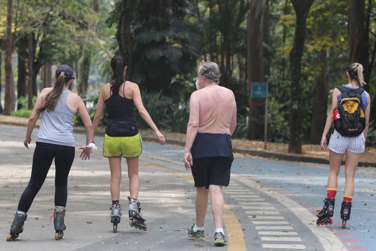 Três mulheres jovens, de costas, andam de patins em uma alameda do parque Ibirapuera usando blusas sem mangas. Também de costas um home de cabelo grisalho caminha sem camisa.