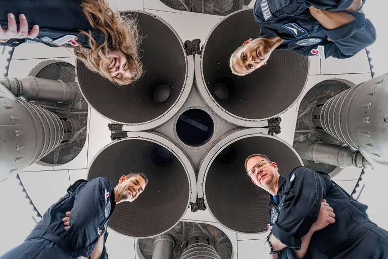 Uma mulher e três homem olhando para a cãmera; ao redor da cabeça de cada um deles está a extremidade de saída do foguete que os levará ao espaço