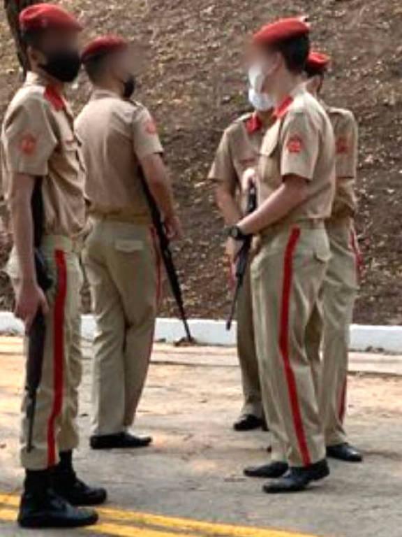 Cinco jovens com uniforme militar seguram espingardas
