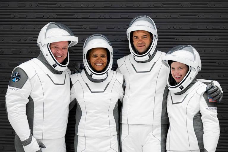 Dois homens e duas mulheres posam de pé em um fundo cinzento vestindo trajes de astronauta, com capacetes com visor por onde podemos ver seus rostos