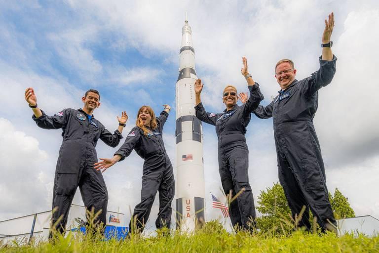 quatro pessoas sorriem diante de um foguete