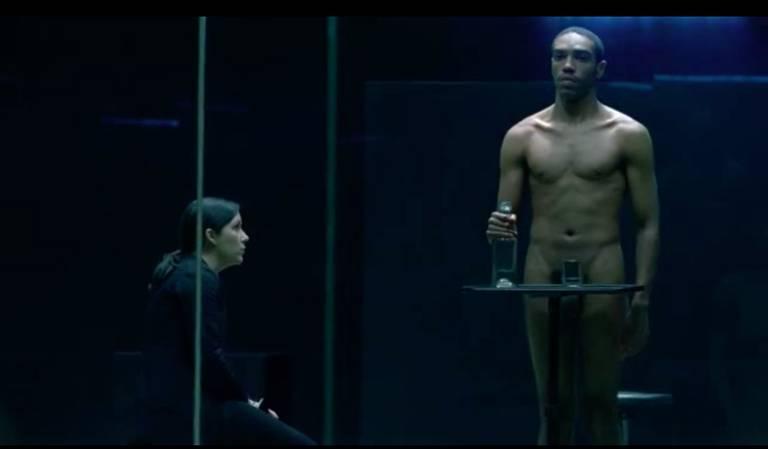 Homem nu numa vitrine é observado por uma mulher que está fora