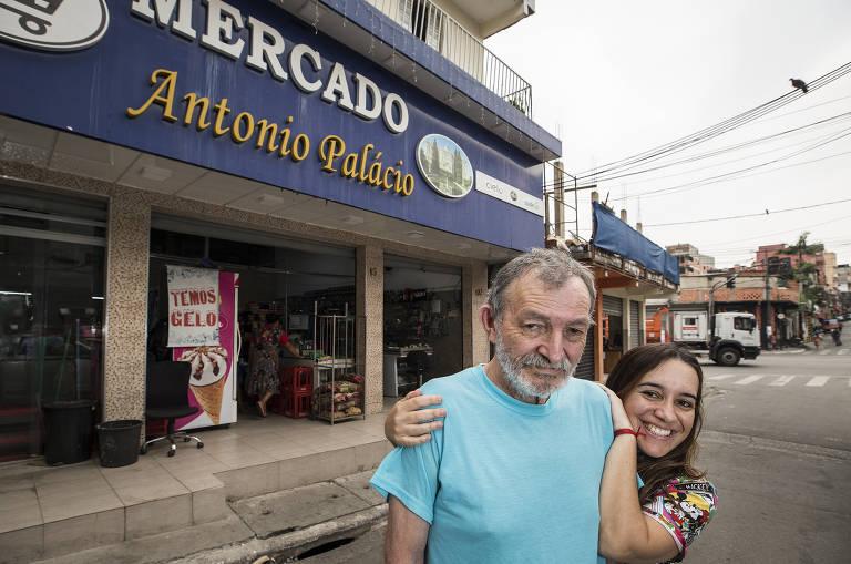 Imagem em primeiro plano mostra Tonho do Palácio sendo abraçado pela filha Tatiana Bastos. Ao fundo, se vê a fachado do comércio da família onde se lê Mercado Antonio Palácio