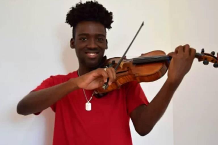 Imagem em primeiroplano mostra jovem negro segurando um violino