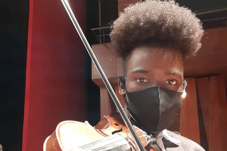 Imagem em primeiro plano mostra jovem negro de máscara segurando um violino
