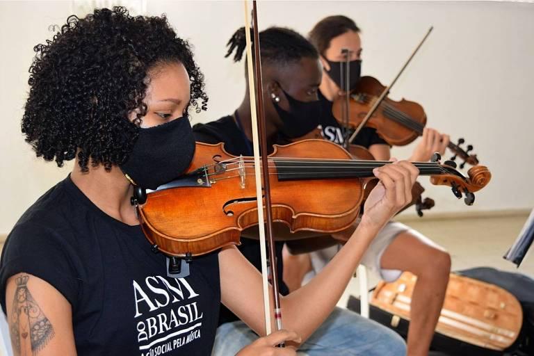 Imagem em primeiro plano mostra uma mulher e dois homens segurando um violino