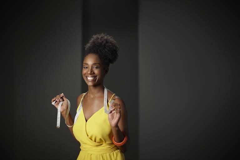 Mulher negra de vestido amarelo e cabelos presos segura fita métrica e sorri em fundo preto