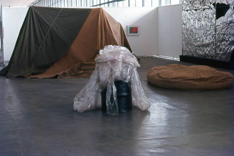 Imagem de obra no pavilhão da Bienal; ela é formada por um barril metálico, que está cheio de plástico