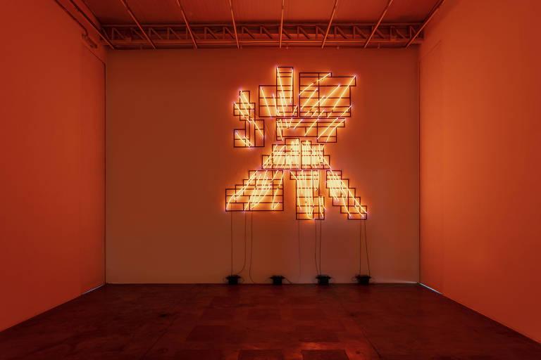 Neon iluminado de cor alaranjada forma imagem que lembra um vulcão em erupção