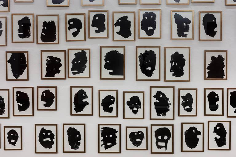 Parede tomada por série de colagens de papel preto recortado que lembram rostos gritando