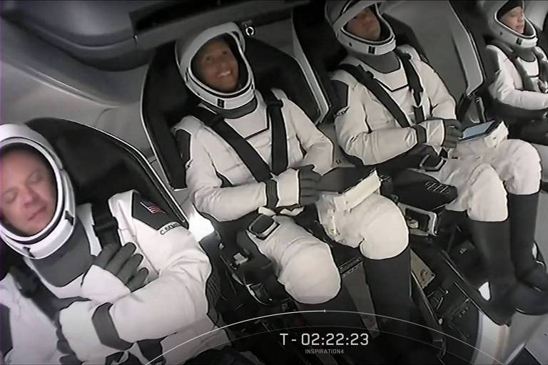 Quatro pessoas sentadas com roupas de astronauta brancas dentro de uma nave com paredes e assentos cor de cinza