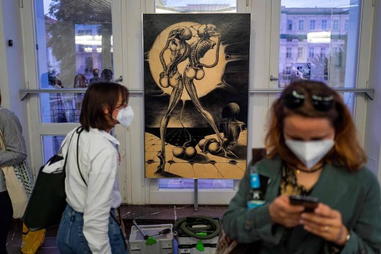 Em primeira plano, mulher de máscara olhando para o celular, com óculos na cabeça; ao fundo, mulher circula perto da obra 'Atomkinder'