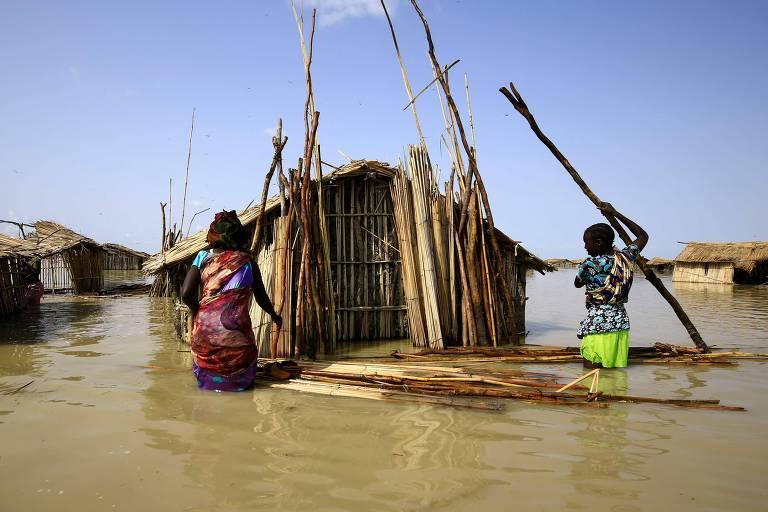Homens reparam cabana semi-submersa