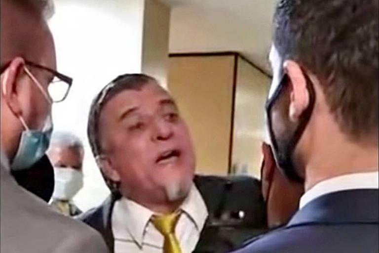 Homem de terno e gravata grita e é segurado por outros dois homens