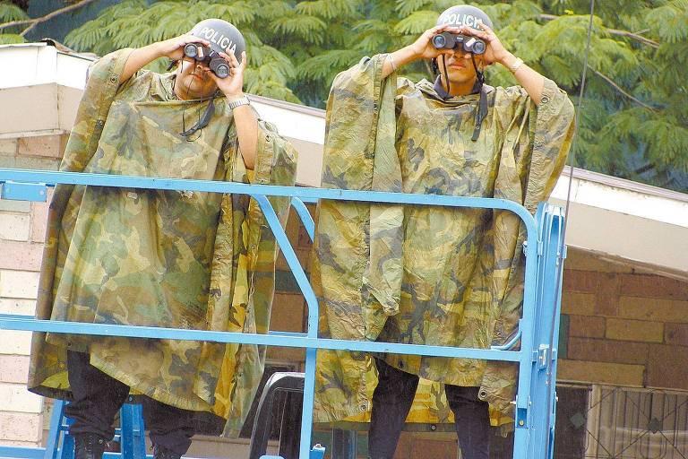 homens fardados usam binóculos para vigiar