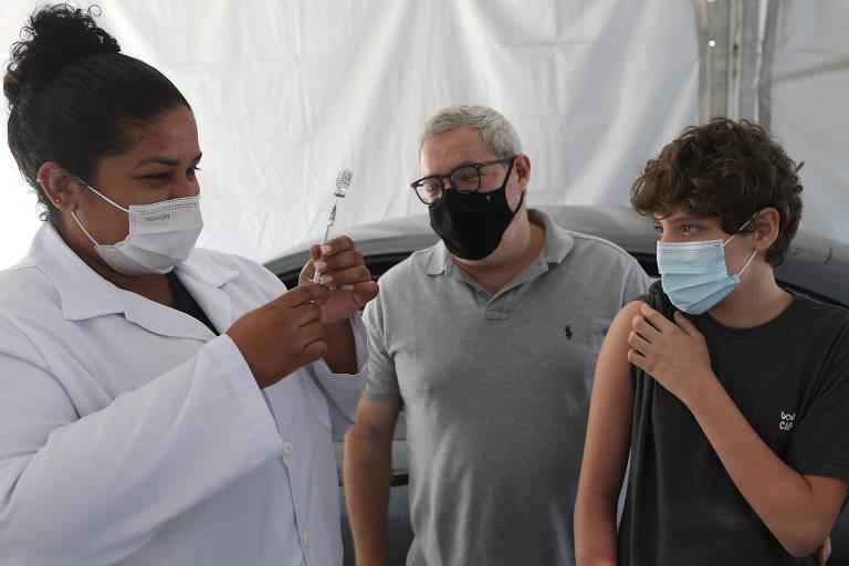 Adolescente de manga arregaçada espera enfermeira aplicar vacina contra Covid
