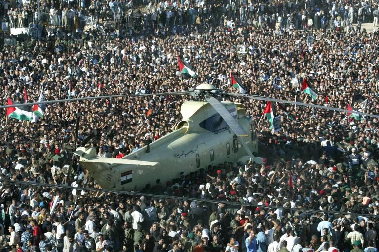 helicóptero militar rodeado por todos os lados por uma multidão tão grande que não se vê o chão; o helicóptero parece flutuar em um mar de gente