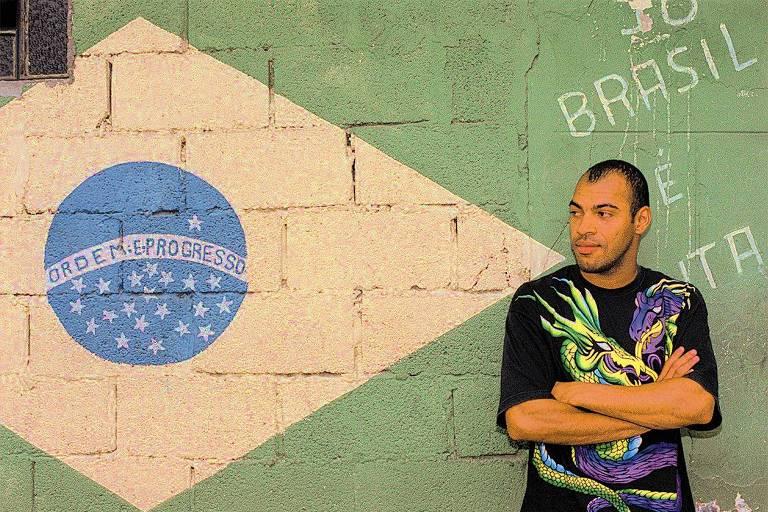 homem pardo está apoiado em um muro em que a bandeira do brasil está pintada; ele está de braços cruzados e olha para o lado