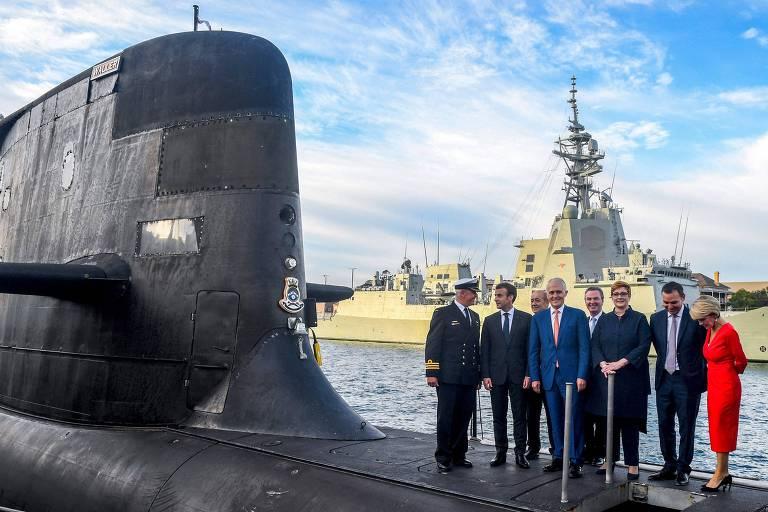 O presidente da França, Emmanuel Macron (segundo da esq. para a dir.), e o então primeiro-ministro australiano, Malcolm Turnbull (centro), sobre o submarino HMAS Waller, da marinha australiana, em Sydney