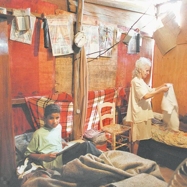 garoto deitado em cama em barraco; atrás dele, uma senhora estende roupa em um varal ao lado de outra cama
