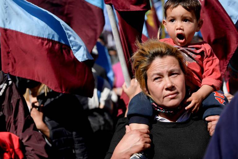 Mulher carrega uma criança, durante passeata em protesto contra o desemprego, a insegurança alimentar e a falta de recursos, em Buenos Aires