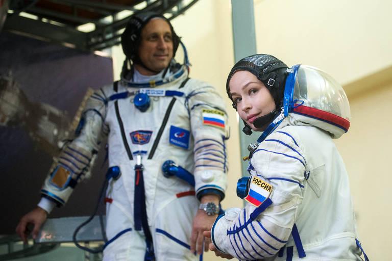 Mulher, em traje de astronauta, olha para trás; próximo a ela, há um homem, também vestido de astronauta