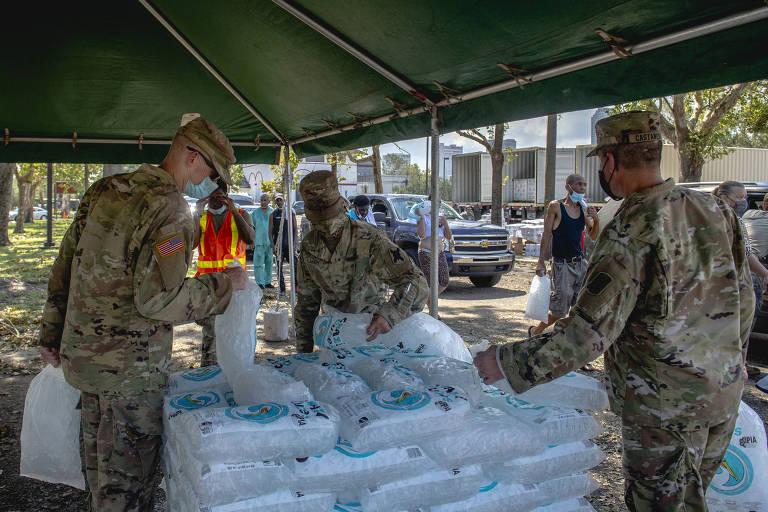 três pessoas vestidas com fardas camufladas estão sob uma tenda em um espaço aberto. no centro da tenda, há sacos cheios de gelo empilhados