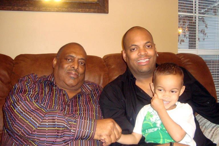 Homem negro vestido com uma camisa com listras coloridas ao lado de outro homem negro mais jovem, vestido com uma camisa preta, e com uma criança sorridente no colo. Os três estão sentados em um sofá. É uma foto de família.