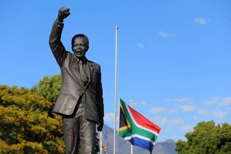 estátua de nelson mandela com o punho erguido; ao fundo, a bandeira vermelha, azul, verde, e preta do país