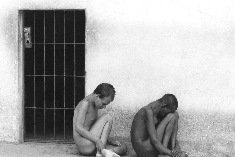 homens nus sentados e encolhidos no chão de concreto; na parede atrás deles, uma porta de cela