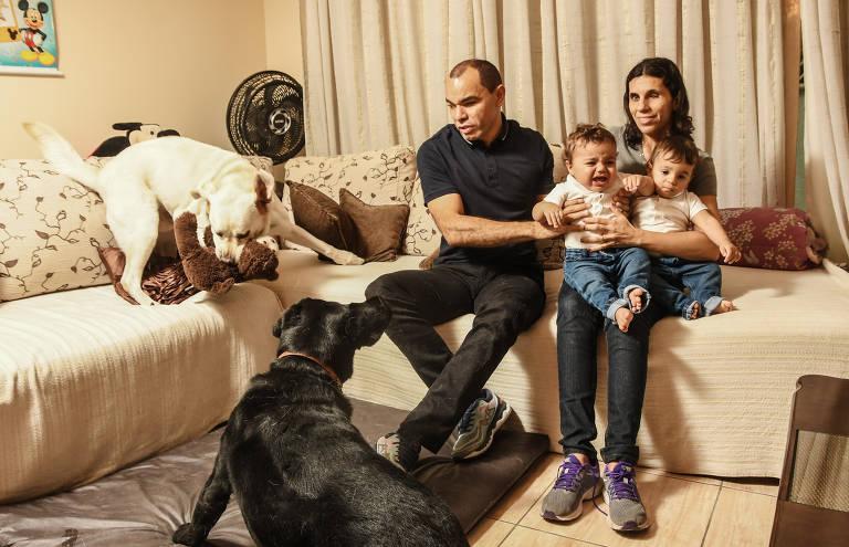 Em uma sala com sofás cor de creme um casal sorri enquanto brinca com dois bebês que estão no colo da mulher. Um cão amarelo também está sobre o sofá e um segundo, de cor preta, observa tudo sentado no chão