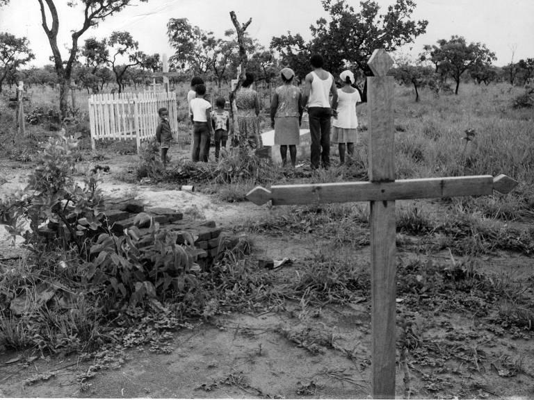 foto em preto e branco mostra cruz de madeira em primeiro plano; ao fundo, uma família rodeia um caixão