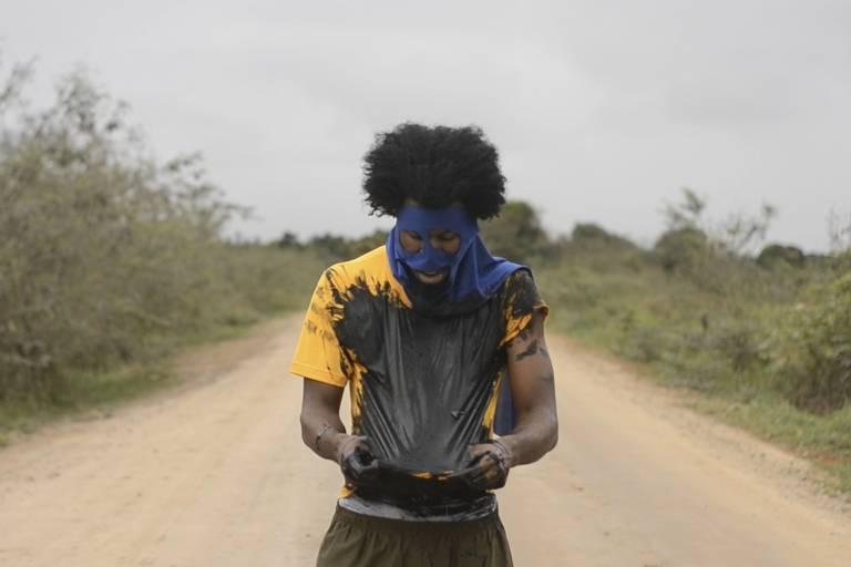 Um homem negro está em uma estrada de terra e veste uma camiseta suja de tinta preta