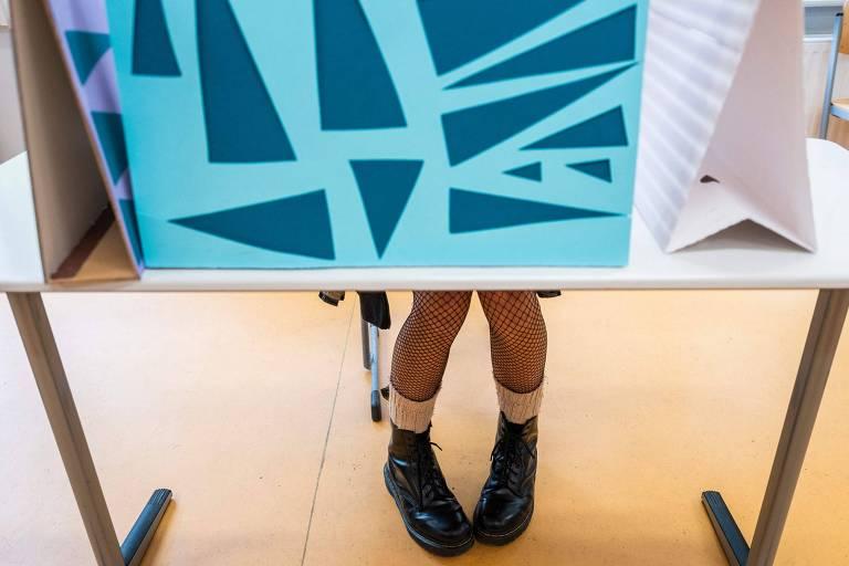 Pernas com meia-calça de rede e botinas pretas são vistas por trás de uma cabine de votação azul com triângulos verdes