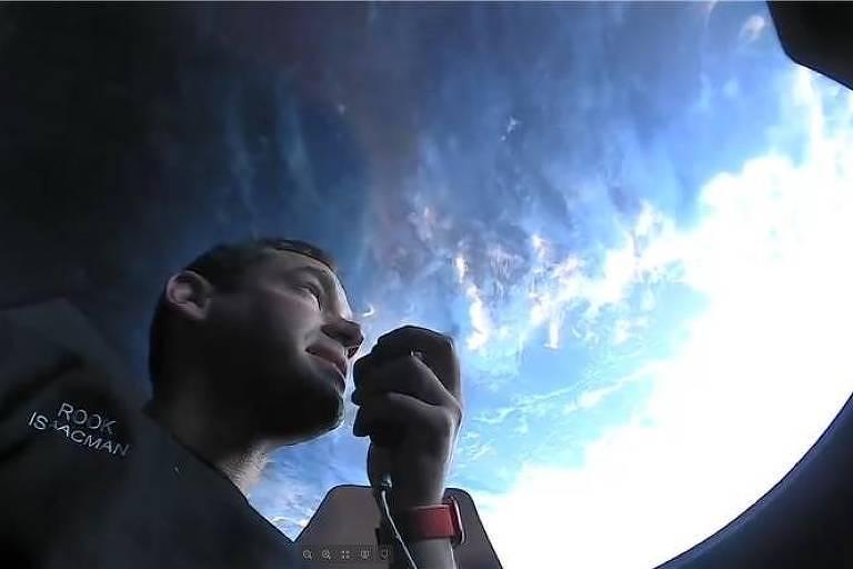 Homem observa o planeta Terra, muito azul, por uma cúpula transparente