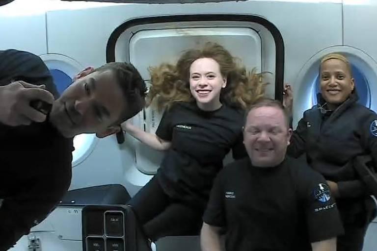 Quatro pessoas sorriem dentro de uma nave espacial com paredes brancas