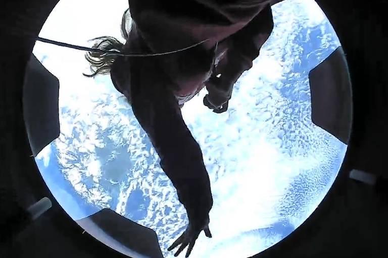 Mulher observa o planeta Terra, muito azul, por uma cúpula transparente