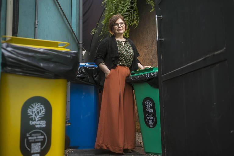 Kelen está em pé em meio a três latas de lixo: uma é verde, outra azul e outra amarela