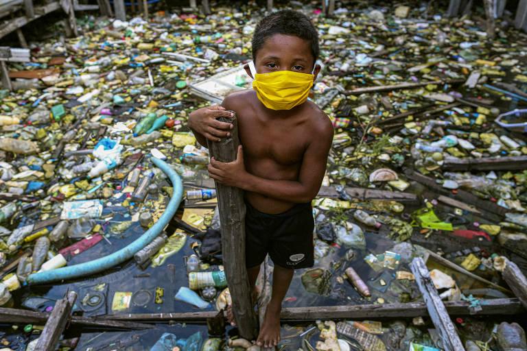 Criança em cima de um rio poluido